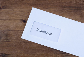 Letter on wooden table. Paper envelope with  insurance claims