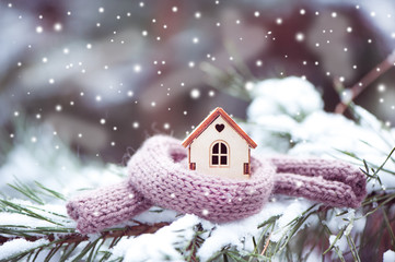 Christmas Toy house is wrapped in a warm scarf, it's snowing.on a natural natural background of a real fir in the snow, toned. Concept of winter, Christmas, new year,