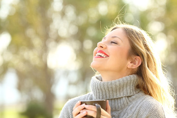 Happy lady breathing fresh air in winter
