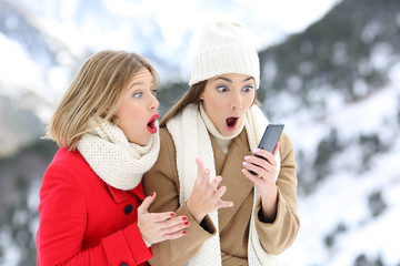 Amazed friends with a smart phone in winter