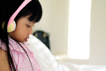 Asian child girl wearing pink headphones in bed room