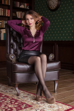 Beautiful woman sits in a brown leather chair, personal assistant, secretary. Business image. Flirt, put your foot on the foot. Business style clothing. To correct hair.