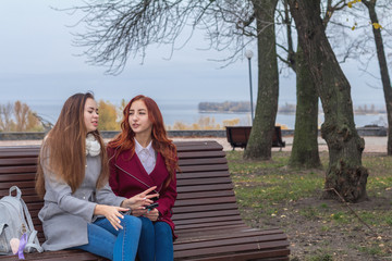 Female teenagers listening to music on smartphone sitting on the bench in an autumn city park
