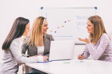 Three businesswomen are having meeting in their office.