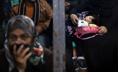 A girl sleeps as she waits with her mother for a travel permit to cross into Egypt through the Rafah border crossing after it was opened by Egyptian authorities for humanitarian cases, in the southern Gaza Strip