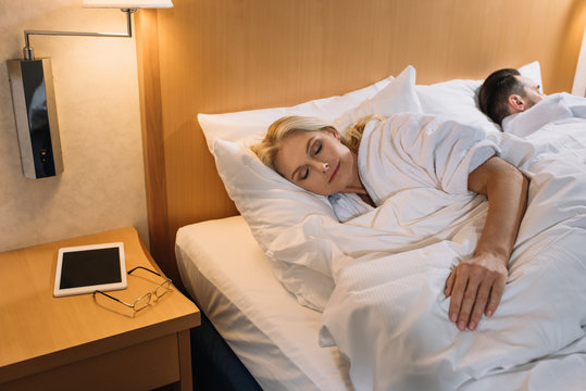 mature couple in bathrobes sleeping in bed and digital tablet with eyeglasses on table in hotel room