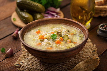Soup with pickled cucumbers and pearl barley - rassolnik on a wooden background.