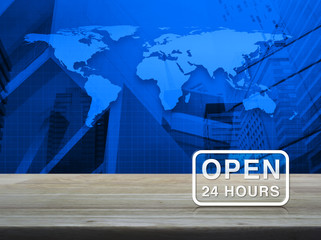 Open 24 hours icon on wooden table over world map and city tower background, Elements of this image furnished by NASA