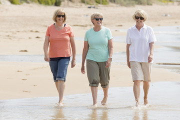 lovely group of three senior mature retired women on their 60s having fun enjoying together happy walking on the beach smiling playful
