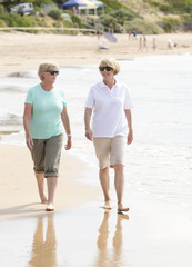 two lovely senior mature retired women on their 60s having fun enjoying together happy walking on the beach smiling playful