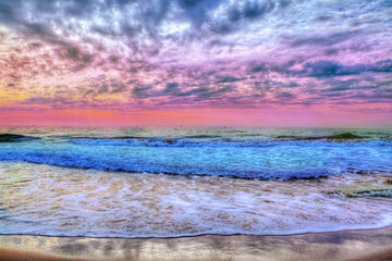 Amazing background with sunset over the beach and colorful clouds and sea