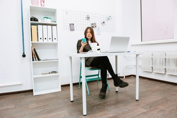 Business creative girl sitting behind a white Desk with a laptop looking at the screen of the phone in the white office