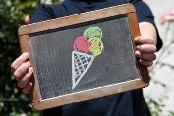 ice cream sketched with chalk on slate shown by young female