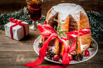Traditional Italian Christmas fruit cake Panettone Pandoro with festive red ribbon and Christmas decorations, gift box and mulled wine, on wooden home background, copy space