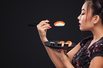Asian woman eating sushi and rolls on a black background.