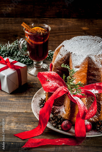 traditional italian christmas fruit cake panettone pandoro with festive red ribbon and christmas decorations gift