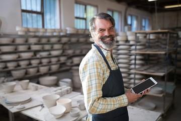 Portrait of male potter using digital tablet
