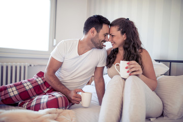 Happy couple in love having romantic breakfast in bedroom.