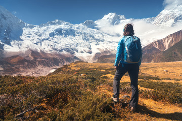 Standing young woman with backpack on the stone and looking on snow covered mountains in clouds at sunset. Landscape with girl, high rocks with snowy peaks, yellow grass, blue sky in Nepal. Travel