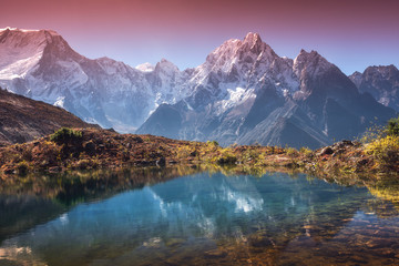 Wall Mural - Beautiful landscape with high mountains with snow covered peaks, sky reflected in lake. Mountain valley with reflection in water in sunrise. Nepal. Amazing scene with Himalayan mountains. Nature