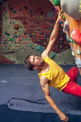 A rock climber is in a bouldering hall.