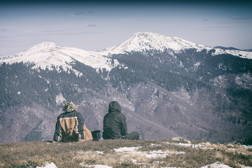 Two people sitting on a hill