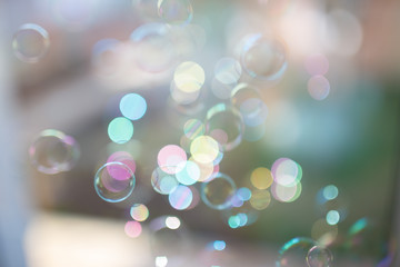 Photo of soap bubbles into the sunlight with beautiful bokeh, pastel colors.
