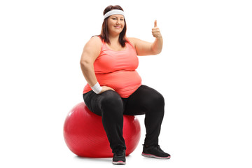 Overweight woman sitting on a pilates ball and making a thumb up sign