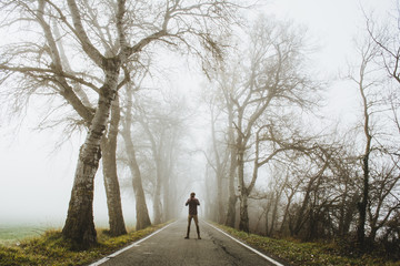 Man standing on foggy road