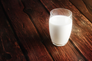 Glass of fresh milk on old wooden background.