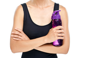 Woman standing with arms crossed and holding sporting plastic bottle