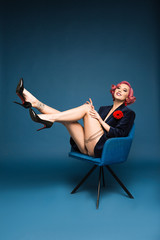 beautiful tattoed pin up girl in jacket with boutonniere posing on armchair infront of blue background