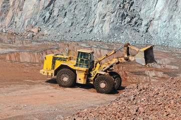 Earthmover in an active quarry mine of porphyry rocks. digging.