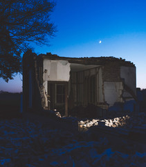 Part of demolished old house in countryside at dusk.