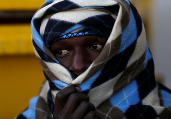 Migrant waits for the MV Aquarius, a search and rescue ship run in partnership between SOS Mediterranee and Medecins Sans Frontieres, to enter Pozzallo on the island of Sicily