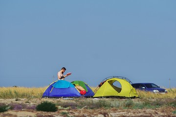 Young men set multi-colored tent in an empty field outside city, under the blue sky, on back blurred background car.