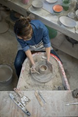 Overhead of female potter molding a clay