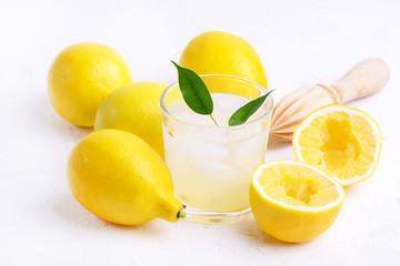Glass ar of Cold Tasty Fresh Lemonade with Ripe Lemons Wooden Squeezer