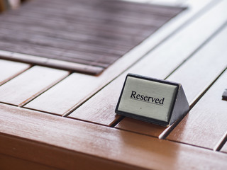Restaurant reserved sign on wooden table