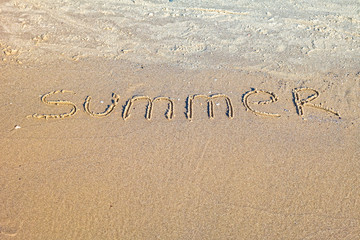 Word Summer written in the sand on the beach.