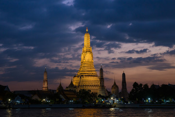 Pagoda at temple of dawn or Wat Arun in Bangkok, Thailand when sunset at twilight with scattered cloud and blue sky in the background and Chao Phraya river in the foreground.