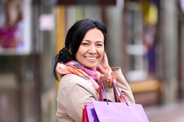 Beautiful mature woman with shopping bags outdoors