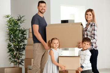 Happy family unpacking things in new flat