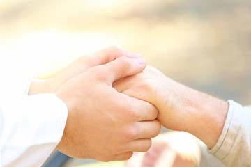 Young caregiver holding hands with senior man, closeup