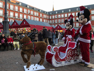 People dressed as Walt Disney characters Mickey Mouse and Minnie in Santa Claus outfits wait to have their photo taken with people at Plaza Mayor square in Madrid
