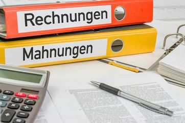 Aktenordner mit der Beschriftung Rechnungen und Mahnungen