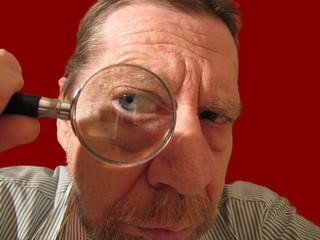 Uomo anziano con lente di ingrandimento.