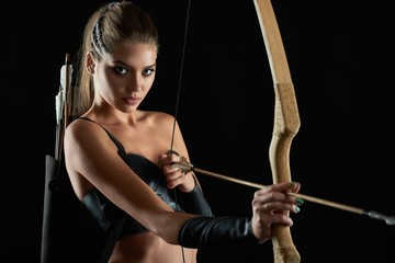 Horizontal portrait of a stunning young sexy female medieval warrior posing with a bow preparing to shoot her enemy with an arrow on black background confidence archer archery historical.