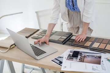 Hands of unrecognisable woman interior designer working with material palette and typing on her laptop.