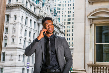 African American Businessman working in New York. Wearing fashionable jacket, black undershirt, necktie, young guy with little goatee, standing by vintage style office building, calling on cell phone.